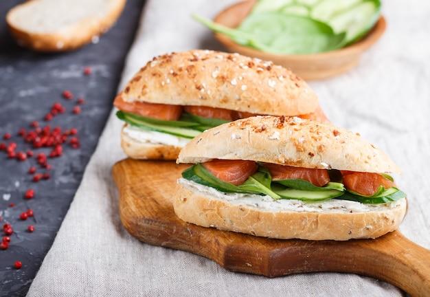Gerookte zalmsandwiches met komkommer en spinazie op houten raad