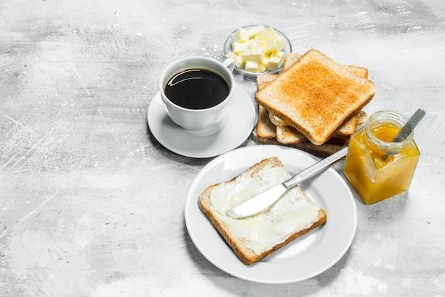 Geroosterd brood met boter en hete koffie.