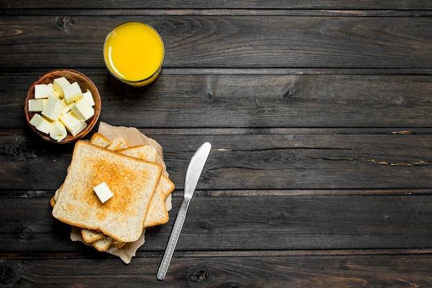 Geroosterd brood met boter en jus d'orange op rustieke tafel