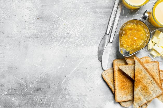Geroosterd brood met boter en sinaasappeljam. op een rustieke achtergrond.