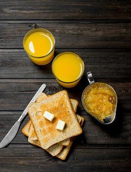 Geroosterd brood met boter, sinaasappelsap en sinaasappelsap.