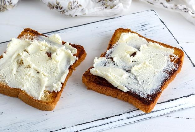 Geroosterd brood met zachte gestremde melk op een witte houten plank
