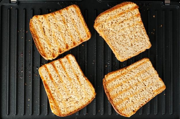 Geroosterd brood op de elektrische grill. klaar sneetjes brood voor het serveren voor het diner.