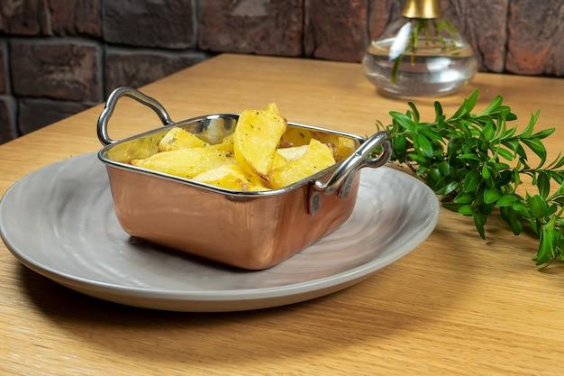 Geroosterd in boter aardappelpartjes met rozemarijn in gouden kom. detailopname. veganistisch eten. lekker garneren. selectieve aandacht. foodfoto voor recept of menu. straatvoedsel