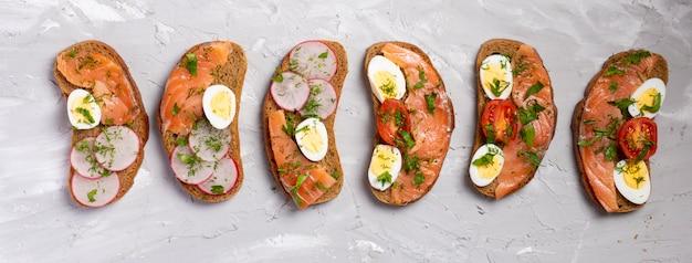 Geroosterd roggebrood met gerookte zalm, radijs en ei-eieren. heerlijke gezonde snack met verse groene groenten op grijze tafel, bovenaanzicht foos