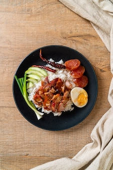 Geroosterd rood varkensvlees in saus op belegde rijst, aziatische voedselstijl