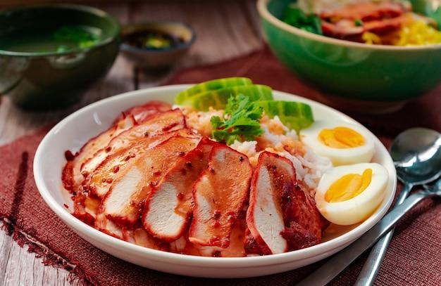 Geroosterd rood varkensvlees met rijst en eiernoedel in groene kom die met gekookt ei dienen