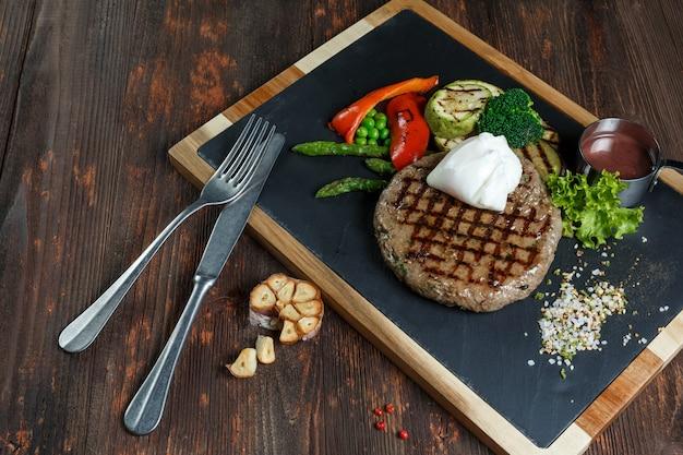 Geroosterd rundvleeslapje vlees dat op barbecue, close-up op donkere houten lijstachtergrond wordt gekookt. vers sappig geroosterd rood vlees op zwarte steenraad, peper en rozemarijn.