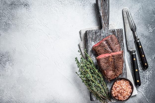 Geroosterd schouderblad of platte ijzeren biefstuk op een houten bord wooden