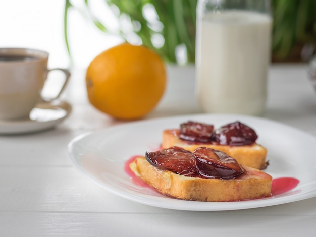 Geroosterd stokbrood met melk, sinaasappelgestremde melk en room op een witte tafel.