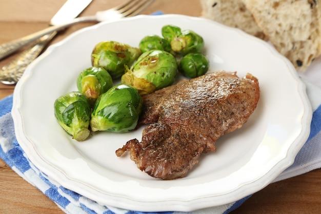 Geroosterd vlees en groenten op plaat, op houten lijstachtergrond