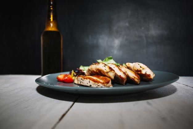 Geroosterd vlees en salade dichtbij fles
