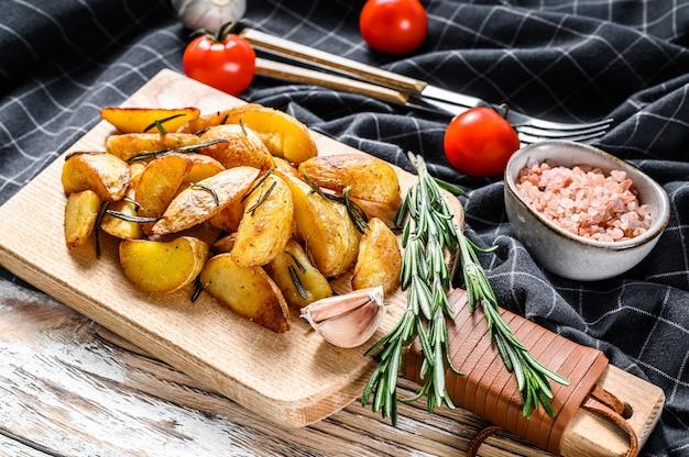 Geroosterde aardappelpartjes met rozemarijn en zout. lekker pittige aardappel. witte achtergrond. bovenaanzicht