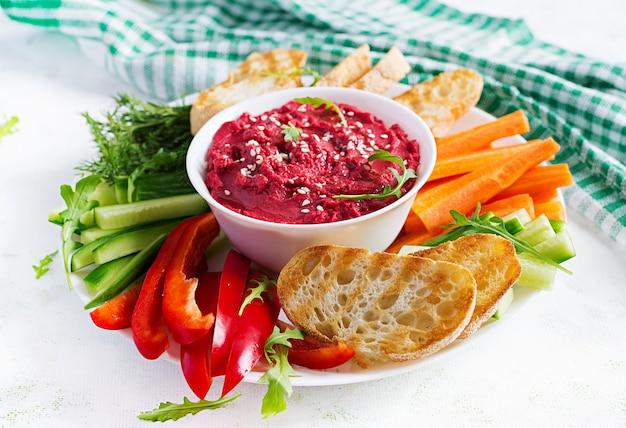 Geroosterde bietenhummus met toast en groenten op een lichte achtergrond. bietenhummus.