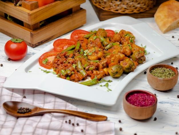Geroosterde bloemkool met spruiten, bonen en geserveerd met tomatensaus en kruiden