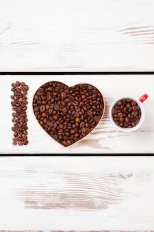 Geroosterde bonen symboliseren liefde voor koffie. zaden gerangschikt in de vorm van een letter en hart.