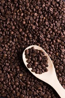 Geroosterde bonen van smaakvolle koffie bovenaanzicht met houten lepel
