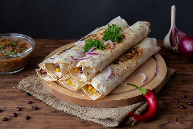 Geroosterde burrito's met kip, rode bonen en maïs.