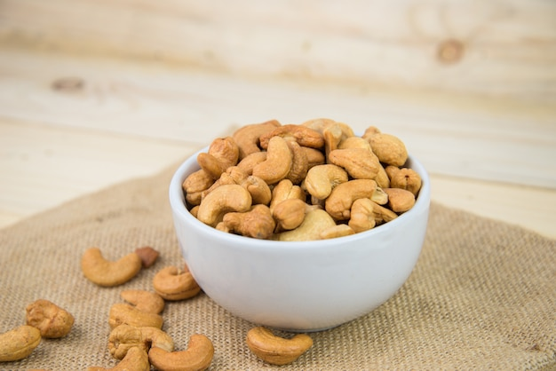 Geroosterde cashewnoot in de witte kom op zakachtergrond. cashewnoot is snack of rauw van kok. gezond eten. lage calorieën of dieetvoeding. cashewnoot met copyspace.