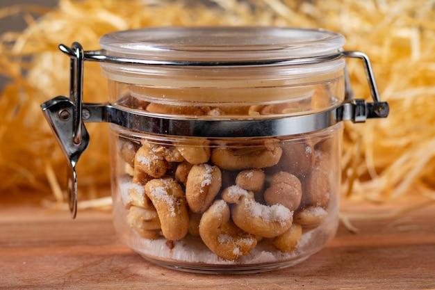 Geroosterde cashewnoten in glascompote met zout, op een houten lijst met een palmstroachtergrond.