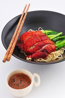 Geroosterde eendnoedel met saus chinese keuken op witte achtergrond