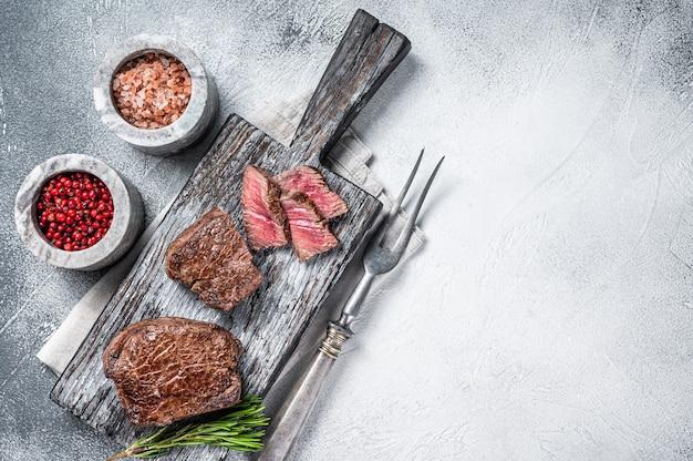 Geroosterde filet mignon of ossenhaas biefstuk op houten snijplank. witte achtergrond. bovenaanzicht. ruimte kopiëren.