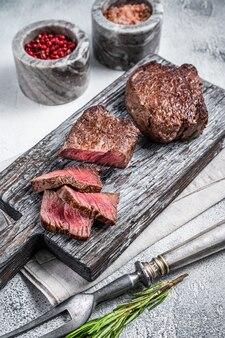 Geroosterde filet mignon of ossenhaas biefstuk op houten snijplank. witte achtergrond. bovenaanzicht.