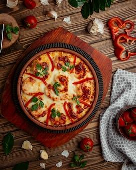 Geroosterde garnalen met kaas, rode paprika in aardewerk pan