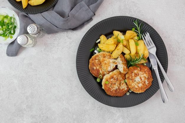 Geroosterde, gebakken aardappelen met kippengehaktballetjes op een zwarte plaat met verse groene uien en rozemarijn.