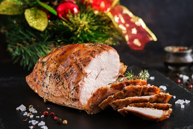 Geroosterde gesneden kerstmisham van turkije op donkere rustieke achtergrond. festival eten.