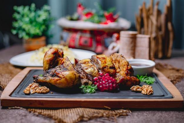 Geroosterde gevulde kip versierd met granaatappel en walnoten op een zwart bord en rijst in een witte plaat op een houten tafel