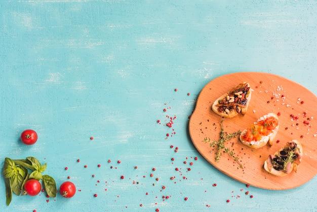 Geroosterde gezonde sandwiches met basilicum; tomaten en rode peperkorrels op gekleurde achtergrond