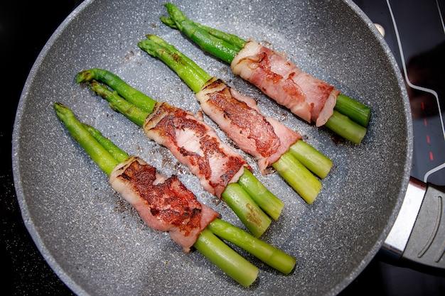 Geroosterde groente en spek op een pan.