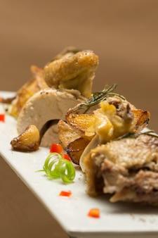Geroosterde haan met aardappelen, met groene kruiden, geplaatst op een witte plaat
