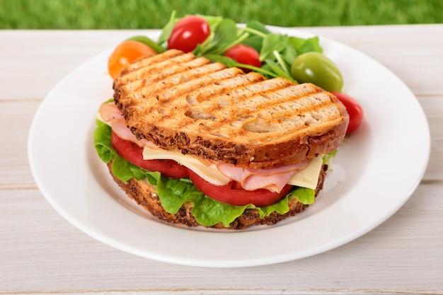 Geroosterde ham en kaassandwich op houten lijst