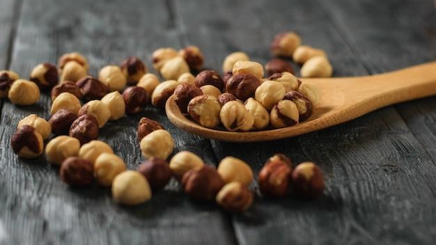 Geroosterde hazelnoten in een lepel op een zwarte houten tafel. bereid met de oogst van hazelnoten.