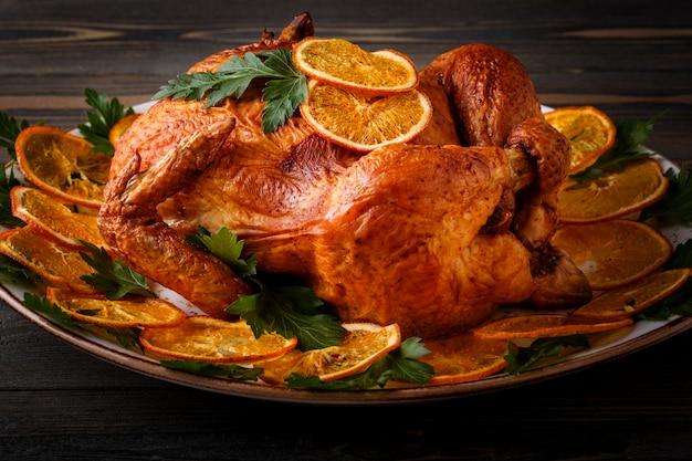 Geroosterde hele kip met peterselie en sinaasappels.