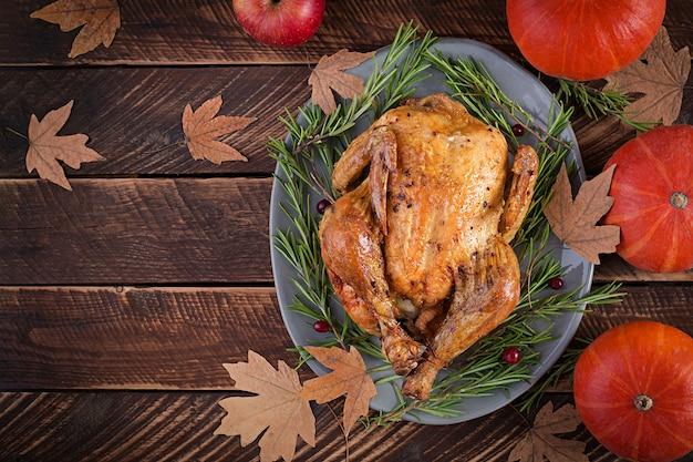 Geroosterde kalkoen gegarneerd met veenbessen op een rustieke tafel versierd met pompoenen, appels en herfstblad. dankdag. plat leggen. bovenaanzicht