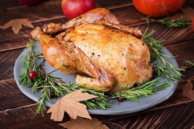 Geroosterde kalkoen gegarneerd met veenbessen op een rustieke tafel versierd met pompoenen, appels en herfstblad. dankdag.