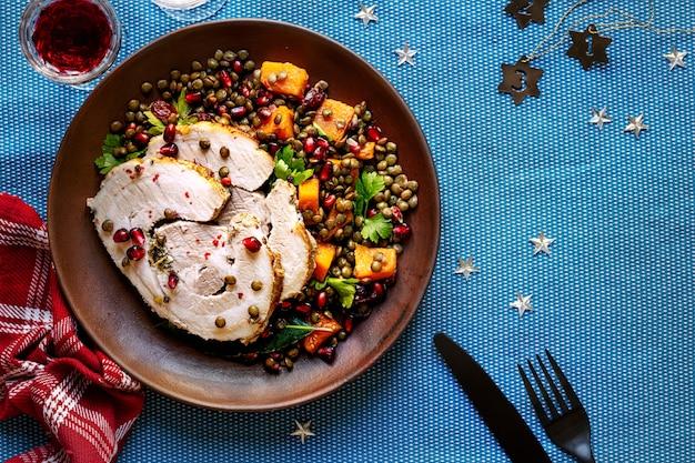 Geroosterde kerstham met granaatappel en linzen foodfotografie