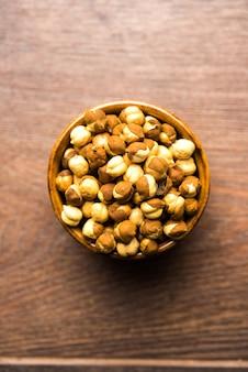 Geroosterde kikkererwten of chana bekend als futana of phutana in het hindi geserveerd in een kom of over een jutezak. selectieve focus