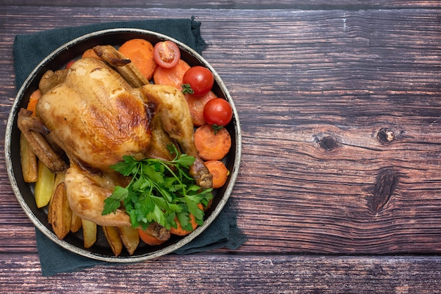 Geroosterde kip, aardappelen en groenten in plaat op donkere houten achtergrond. bovenaanzicht. met kopie ruimte