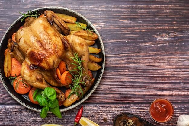 Geroosterde kip, aardappelen en groenten in plaat op donkere houten achtergrond. bovenaanzicht. met kopie ruimte Premium Foto
