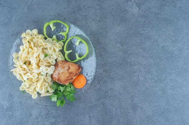 Geroosterde kip en smakelijke pasta op glasplaat.