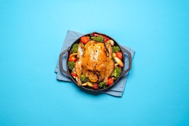 Geroosterde kip met groenten in een gietijzer