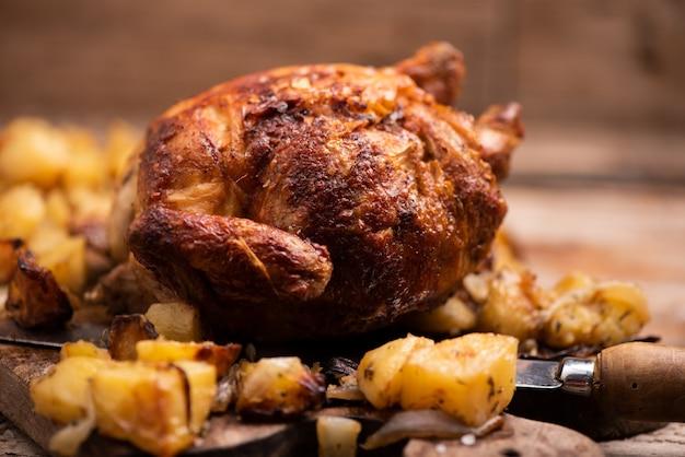 Geroosterde kip op houten bord met frietjes