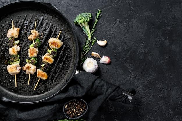 Geroosterde kipfilet spiesjes. broccoli. zwarte achtergrond. bovenaanzicht. ruimte voor tekst