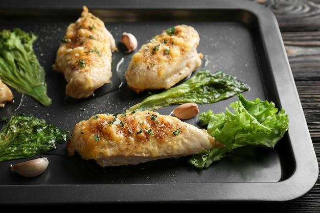 Geroosterde kipfilets met sla op bakplaat