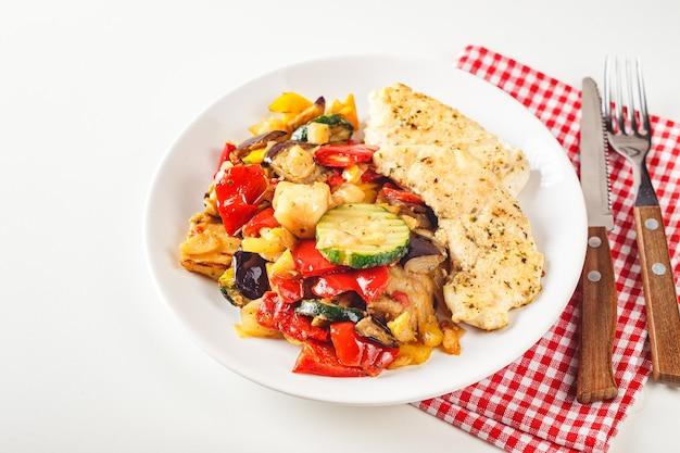 Geroosterde kippenborst met gegrilde courgette, aubergine en rode en gele paprika op witte plaat met wijnglas.