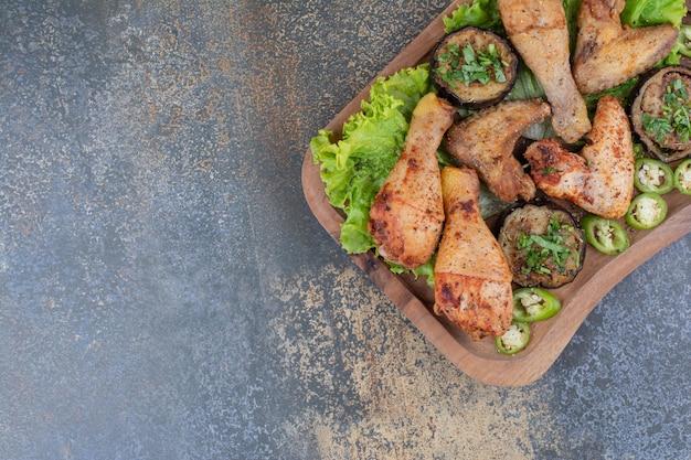 Geroosterde kippenpoten en vleugels op een houten bord met sla en peper. hoge kwaliteit foto